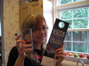 Lesley holds Flying Saucer Obama Glass and political door hanger